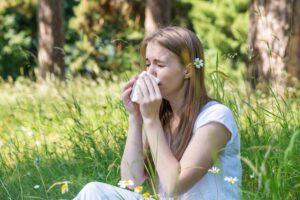 Leidet man unter Allergien, wie diese Frau in der Wiese, können diese auch eine Bindehautentzündung auslösen