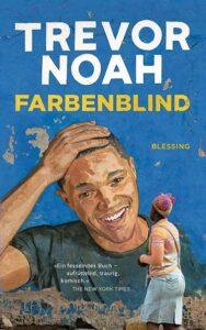 Titelbild des Buches Farbenblind von Trevor Noah. Das gemalte Wandporträt von Trevor Noah zeigt ihn, wie er sich lächelnd an den Kopf fast. Vor dem Gemälde läuft eine dunkelhäutige Südafrikanerin in traditioneller Kleidung vorbei.