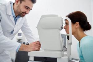 Patientin im mittleren Alter hat ihr Kinn auf dem Tonometer aufgestützt und schaut in das Messgerät. Der Augenarzt nimmt die Messung vor.