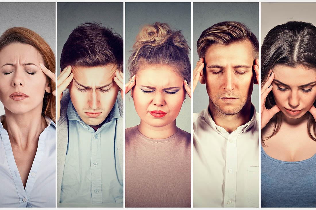Drei Frauen und zwei Männer im mittleren Alter nebeneinander. Alle halten ihre Hände an die Schläfen. Ihr Gesichtsausdruck zeigt, dass sie Kopfschmerzen plagen.