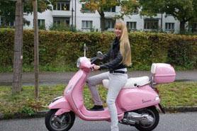 Saskia Siegenthaler sitzt lächelnd und mit einem Bein auf dem Boden auf ihrer rosaroten Vespa.