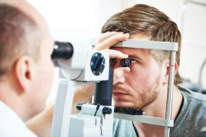 Mann hat sein Kinn auf Opthalmologischem Gerät aufgestützt und schaut nach oben. Der Augenarzt untersucht ihn, indem er durch das Opthalmolgogische Gerät schaut. Er hält zusätzlich ein spezielles Glas vor das Auge des Patienten, um die Netzhautablösung untersuchen zu können.