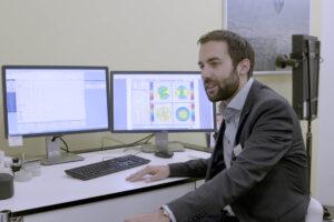 Doktor Müller im Praxiszimmer der Voruntersuchung vor zwei PC-Bildschirmen.