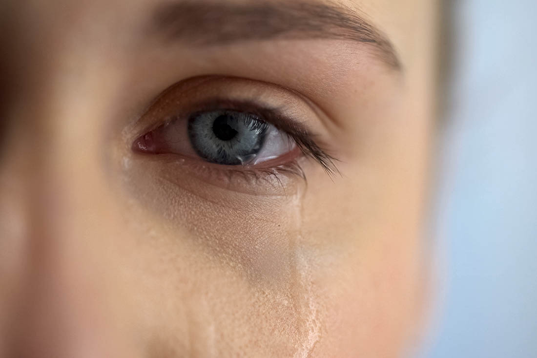 In Grossaufnahme ein weinendes, blaues Auge einer jungen Frau