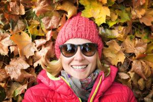 Frau mittleren Alters liegt mit roter Strickmütze, Sonnenbrille, Schal und roter Winterjacke im Herbstlaub und lacht.