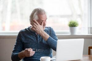 Mann mit grauen Haaren sitzt vor einem Notebook und reibt sich mit dem Daumen der linken Hand die Augen. Seine Brille hält er in der rechten.
