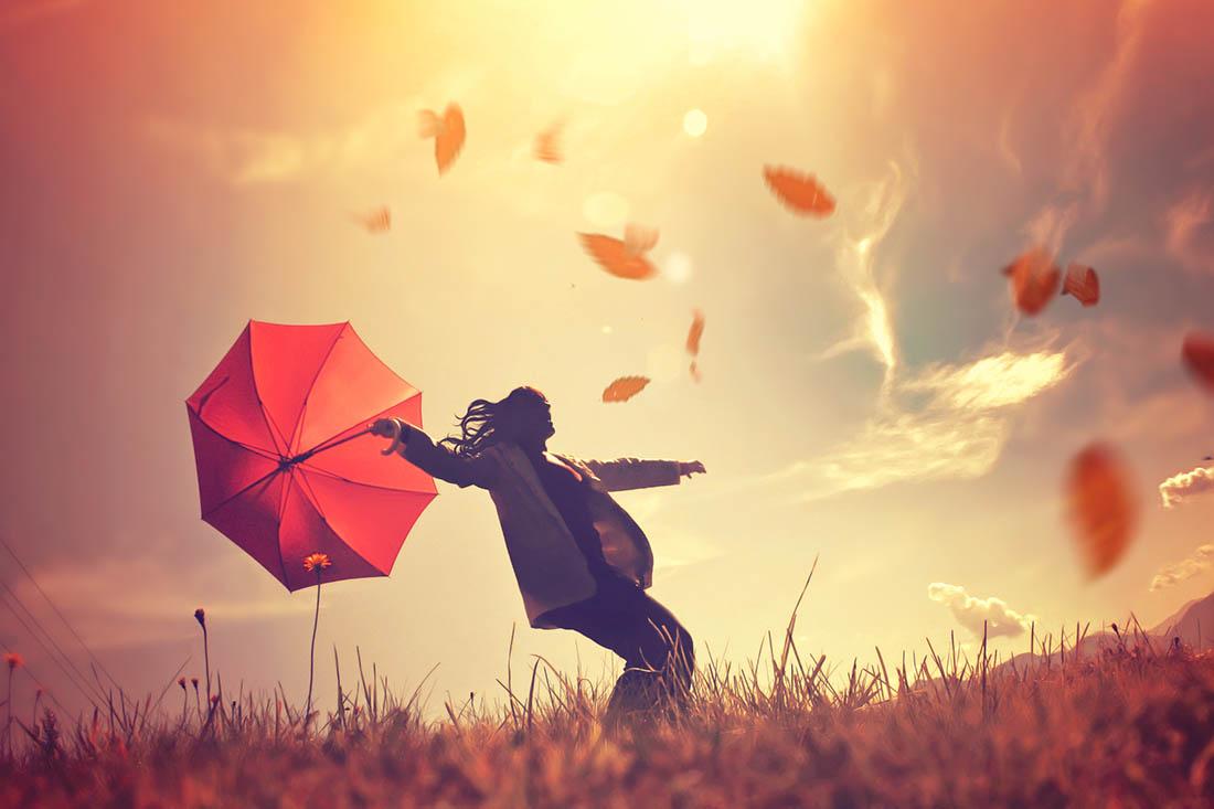 Eine Frau mit rotem, aufgespantem Schirm läuft im Schein der Herbstsonne über eine Wiese. Der Wind bläst ihr entgegen und orange Blätter wirbeln durch die Luft.