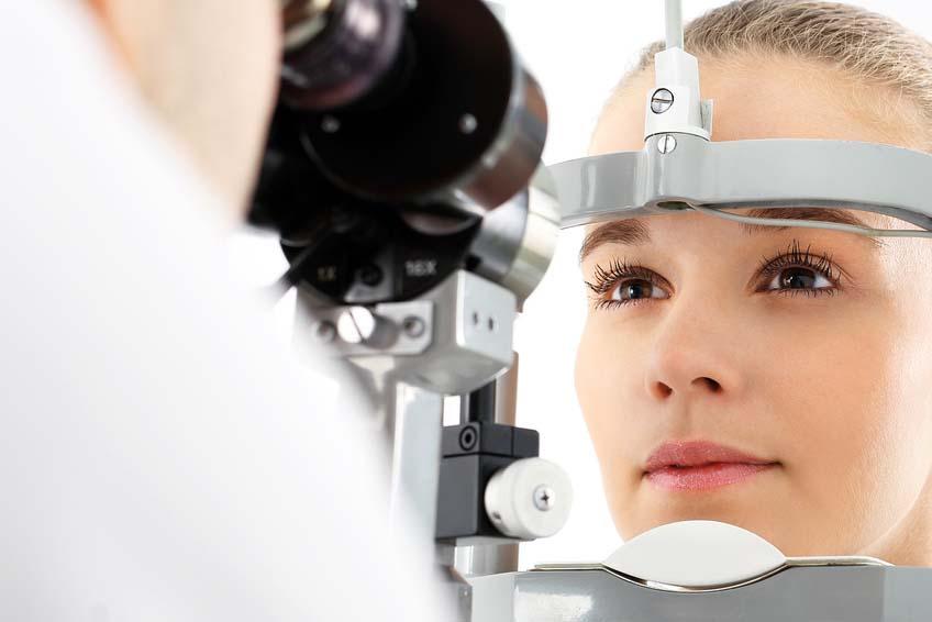Blonde, junge Frau schaut beim Optometrist in ein Augenmessgerät