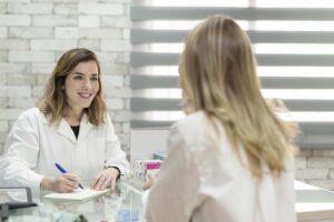 Patientin und Ärztin sind im Gespräch, Ärztin schreibt dabei