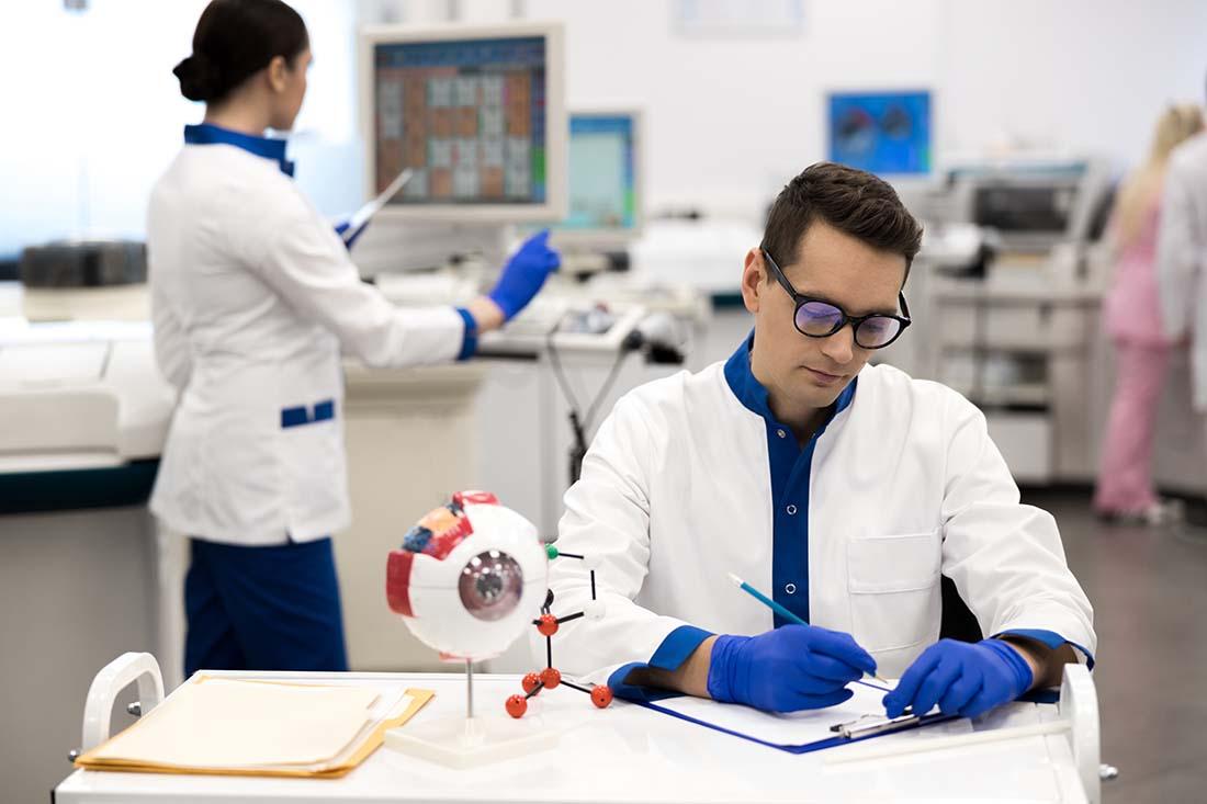 Männlicher junger Forscher schreibt auf ein Klemmbrett, junge weibliche Forscherin im Hintergrund arbeitet stehend am PC