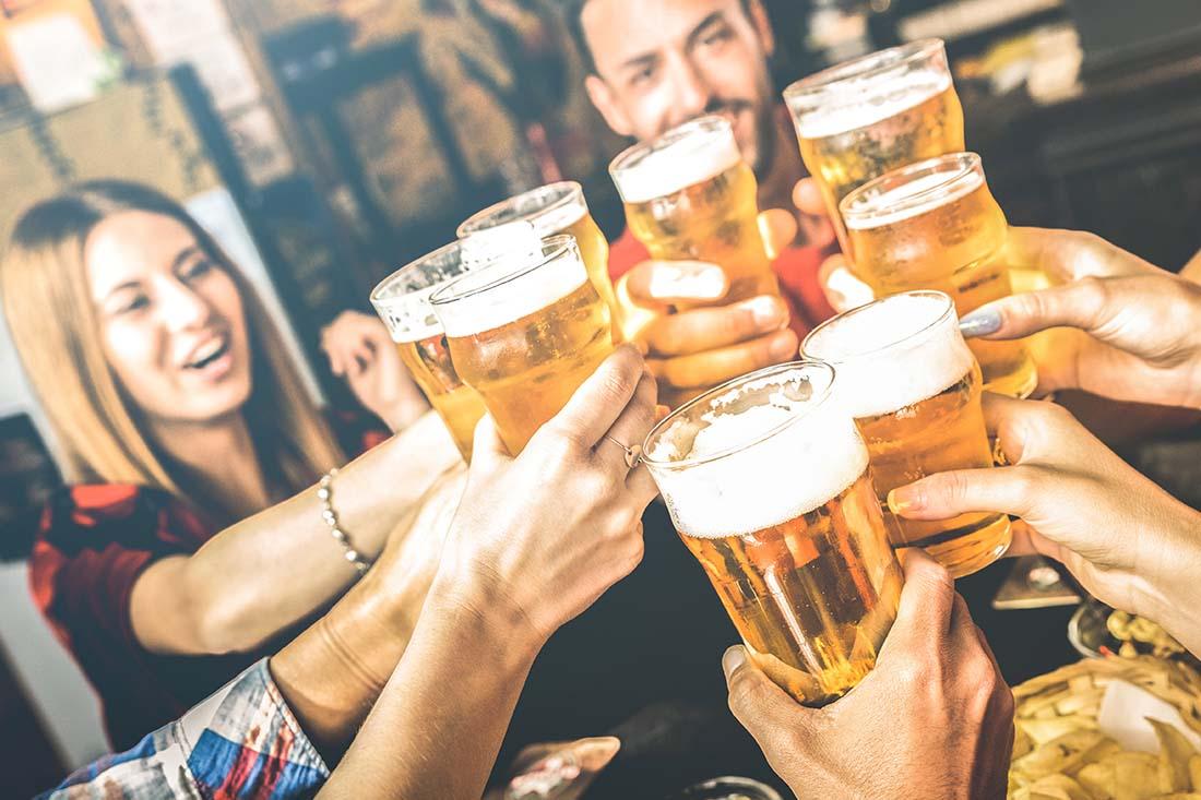 Eine Gruppe junger Personen stosst mit Bier an. Die Hände mit dem Bier sind im Vordergrund, im Hintergrund sind verschwommen eine Frau und ein Mann.