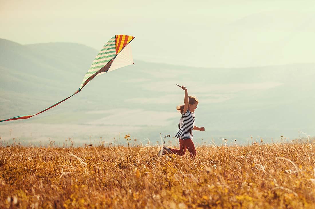 Mädchen rennt bei Tageslicht mit einem Drachen durch ein Getreidefeld
