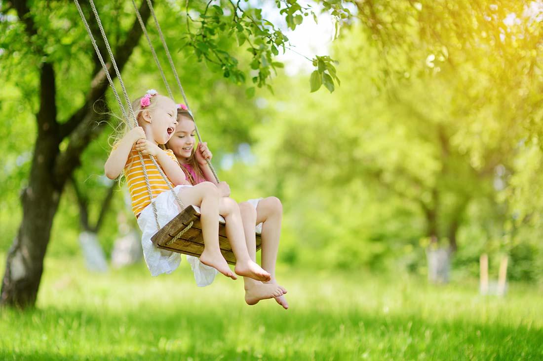 Zwei Mädchen sitzen auf einer Holzschaukel im sommerlichen Garten. Sie lachen und haben Spass.