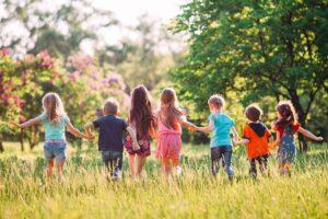 Sieben Kinder rennen Hand in Hand an einem sonnigen Tag über eine Wiese. Man sieht sie von hinten.