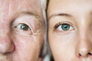 Grossmutter und erwachsene Enkeltochter blicken Wange an Wange mit ihren grünen Augen in die Kamera
