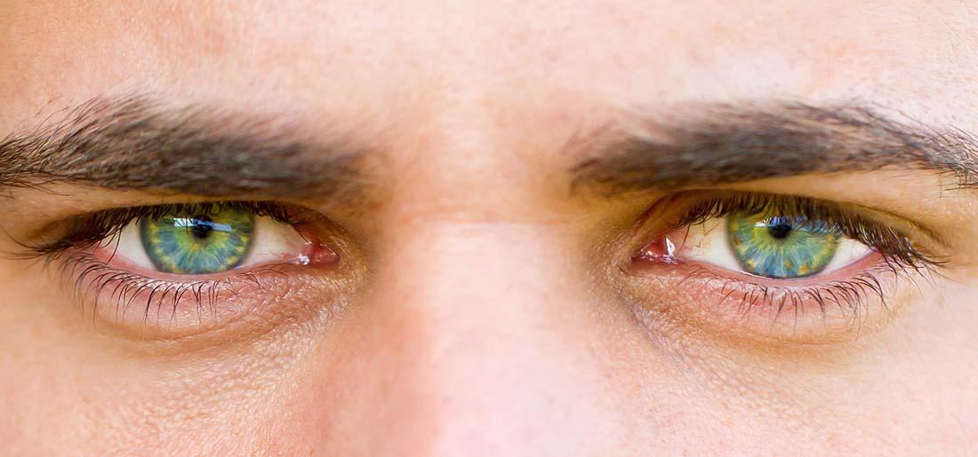 Junger Mann mit stechend grünen Augen blickt in die Kamera