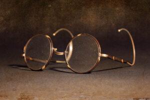 Alte Brille mit braunem Metallgestell und kreisrunden Gläsern.