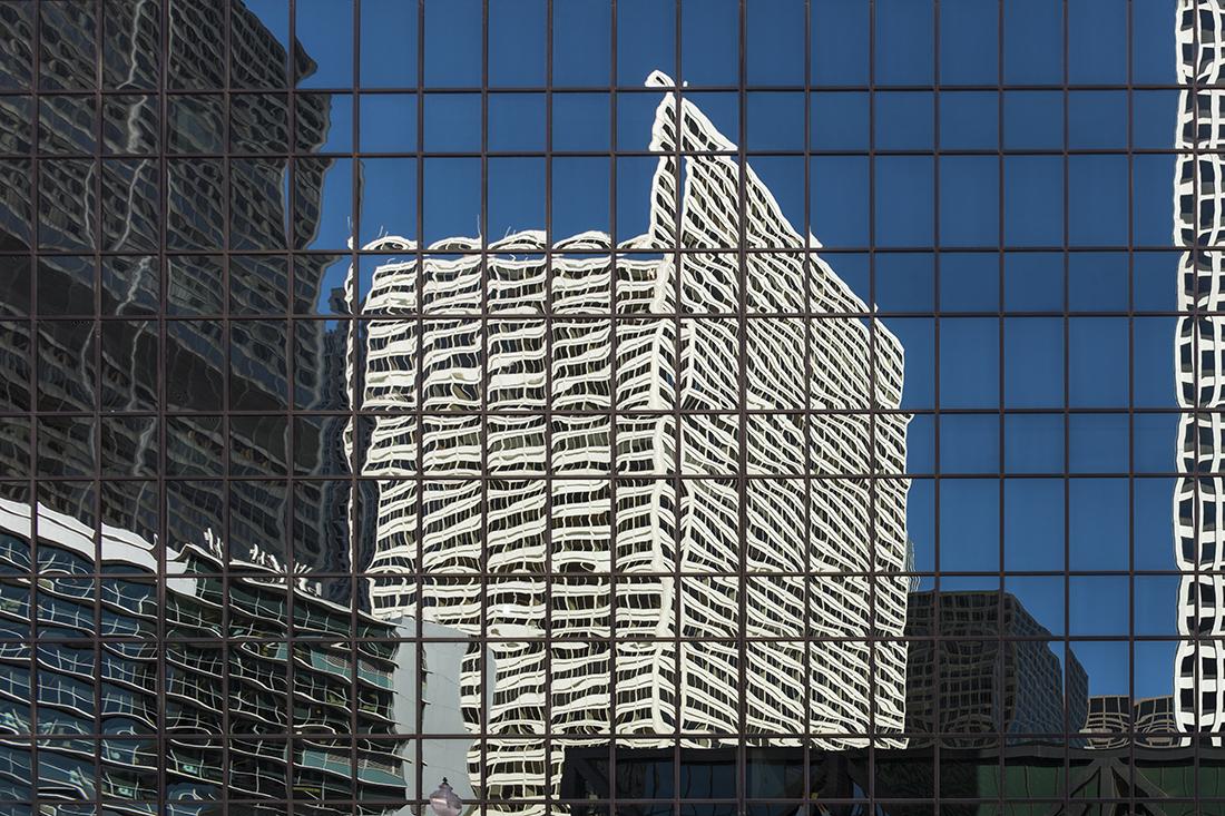 Ausschnitt von unzähligen Fenstern eines Hochhauses. Darin spiegelt sich ein anderes weisess Hochhaus. Die Fensterlinien erscheinen wellenförmig.
