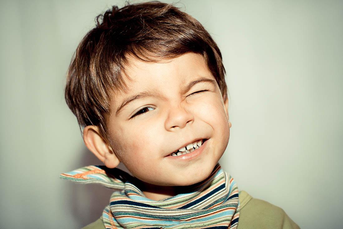 Dreijähriger Junge blinzelt. Er kneift linkes Auge zusammen und lacht.
