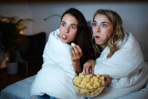 Zwei junge Frauen schauen mit grossen, aufgerissenen Augen auf einen Fernseher. Dieses ist nicht sichtbar. Dabei essen sie geistesabwesend Snacks aus einer Schüssel. Sie haben eine Bettdecke um sich gewickelt.