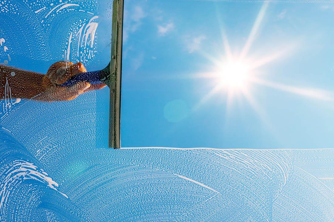 Eine Hand mit Fensterputzgerät zieht von rechts nach links über die Fensterscheibe. Da, wo geputzt wurde, ist die Sicht klar, entspiegelt und ohne Schaum. Die Sonne scheint entgegen.