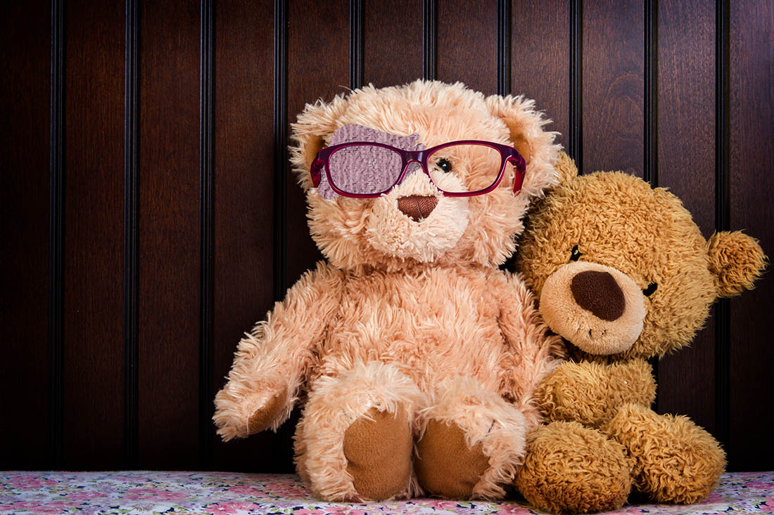 Ein grosser und ein kleiner brauner Teddybär sitzen eng gekuschelt neben einander vor einer Holzwand. Der linke, grössere Teddybär trägt ein Augenpflaster und eine Brille.