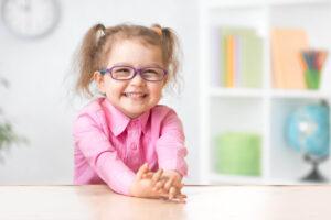 Dreijähriges Mädchen sitzt lachend mit ihrer Brille am Tisch. Sie trägt ein rosa Hemd und zwei Haarzöpfe.
