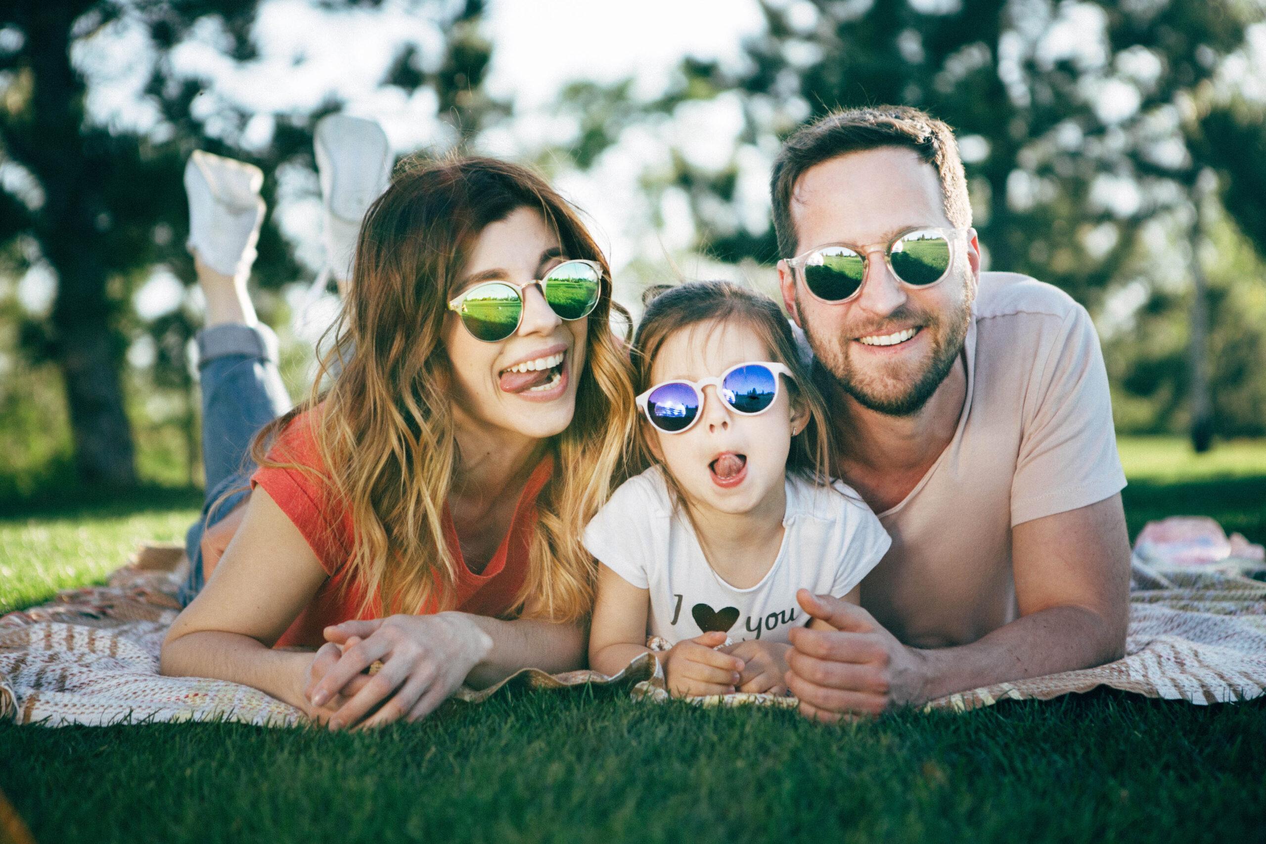 Mutter, Vater und fünfjährige Tochter liegen in einem Park auf einer Sommerdecke. Sie tragen alle eine Sonnenbrille und lachen in die Kamera. Tochter und Mutter strecken die Zunge lustig raus. Der Vater lacht.