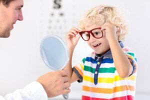 Vierjähriger Junge mit blonden locken und bunt gestreiftem Hemd setzt sich beim Optiker selber eine rote Brille auf und schaut fröhlich lachend in den Spiegel, der ihm der Optiker entgegen hält.