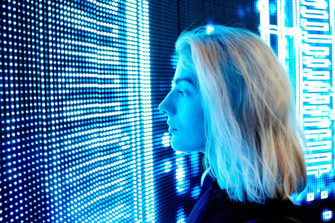 Blonde, junge Frau stet nur ein paar Zentimeter vor einem riesen grossen LED-Bildschirm und schaut rein. Das LED-Licht reflektiert blau.