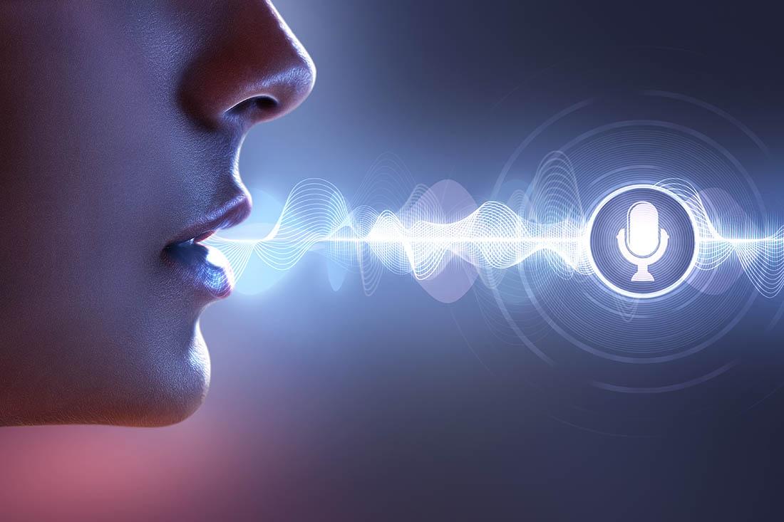 Nase und Mund eines Profils vor dunkelblauem Hintergrund. Abstrakte Frequenzwellen verbinden Mund mit Sprachsteuerungs-Icon.
