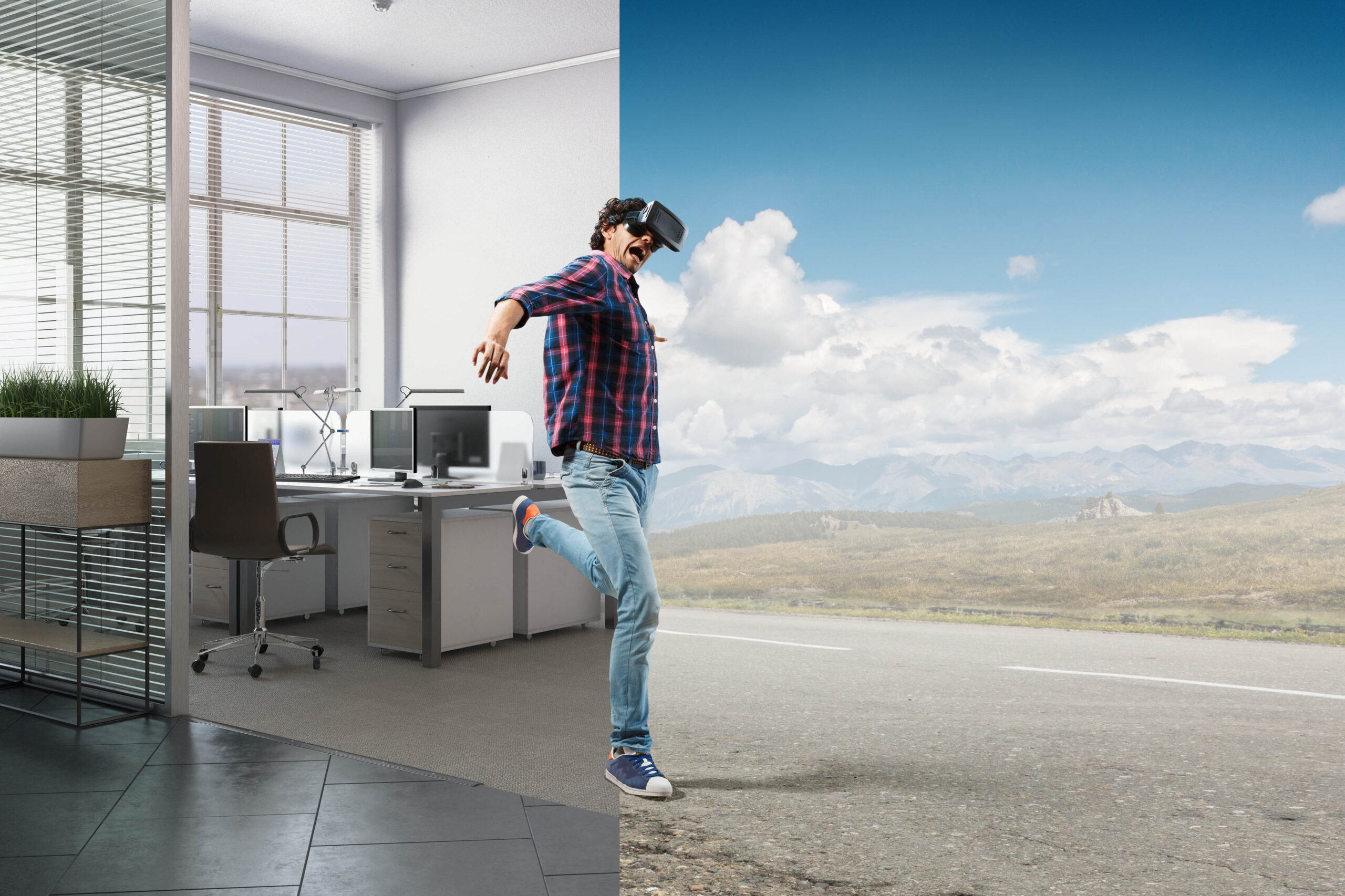 Junger Mann in Jeans und Karo-Hemd trägt Virtual Reality Brille. Er springt von seinem Büro in die virtuelle Welt, die einer amerikanischen Landschaft mit Highway gleicht.