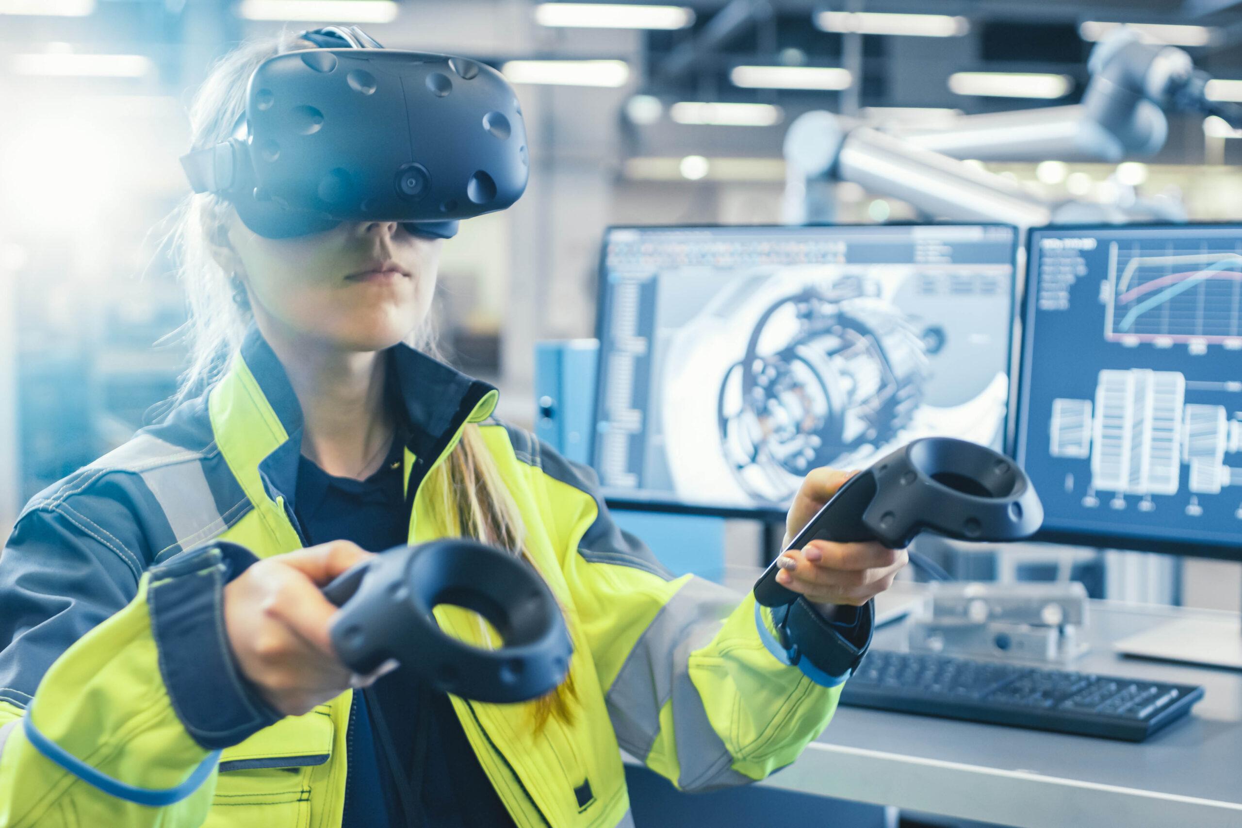 Industrie Igenieurin trägt eine Virtual Reality Brille und hält in beiden Händen jeweils ein Steuerungsgerät. Im Hintergrund sind ihre beiden Bildschirme, auf denen im CAD-Programm Prototypen von Maschinen abgebildet sind.