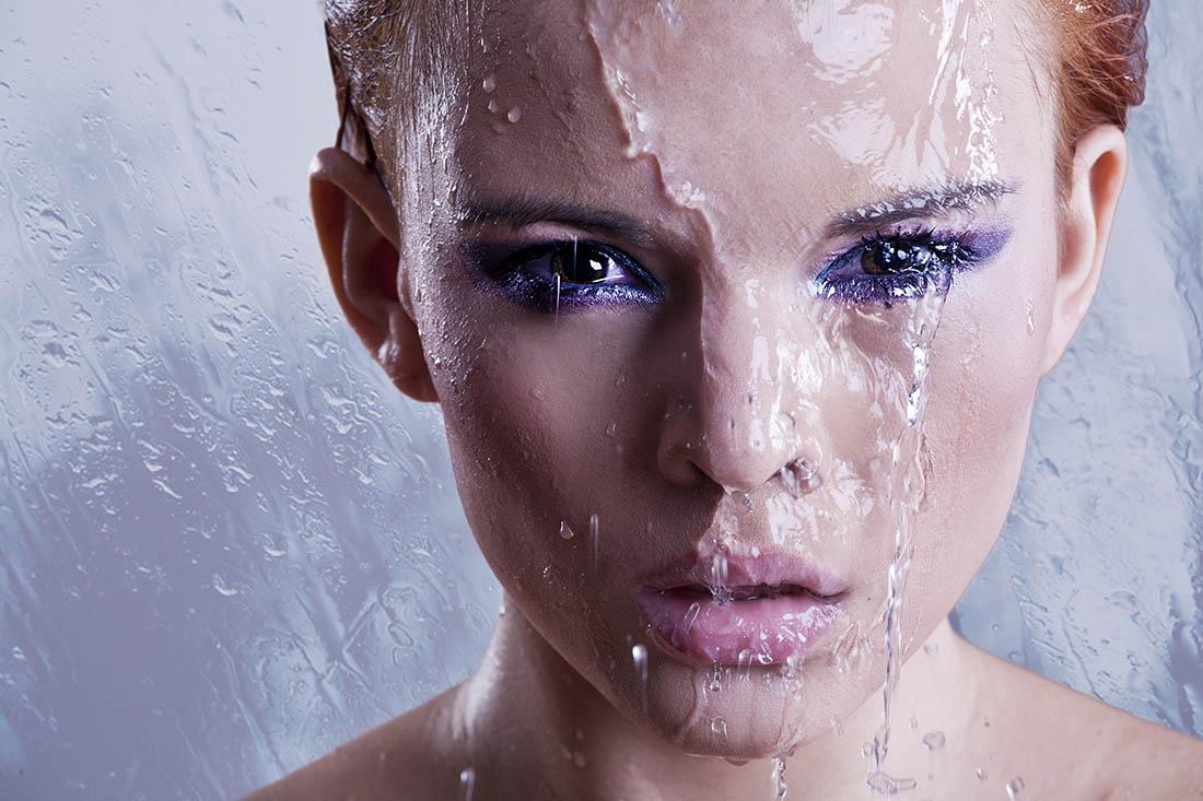 Einer mit wasserfestem Make-up geschminkter Frau läuft von oben Wasser über das Gesicht. Das Make-up verläuft nicht.