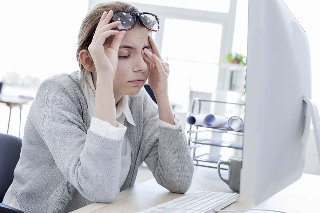 Müde Frau sitzt vor dem Computerbildschirm und reibt ihre Augen.