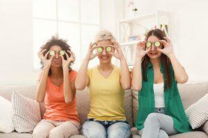 Drei lachende Frauen sitzen nebeneinander auf dem Sofa und halten Gurkenscheiben vor ihre Augen.