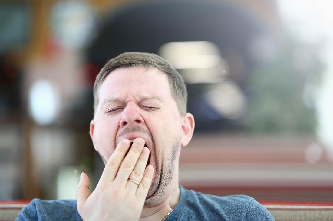 Mann gähnt herzhaft mit Hand vor dem Mund.