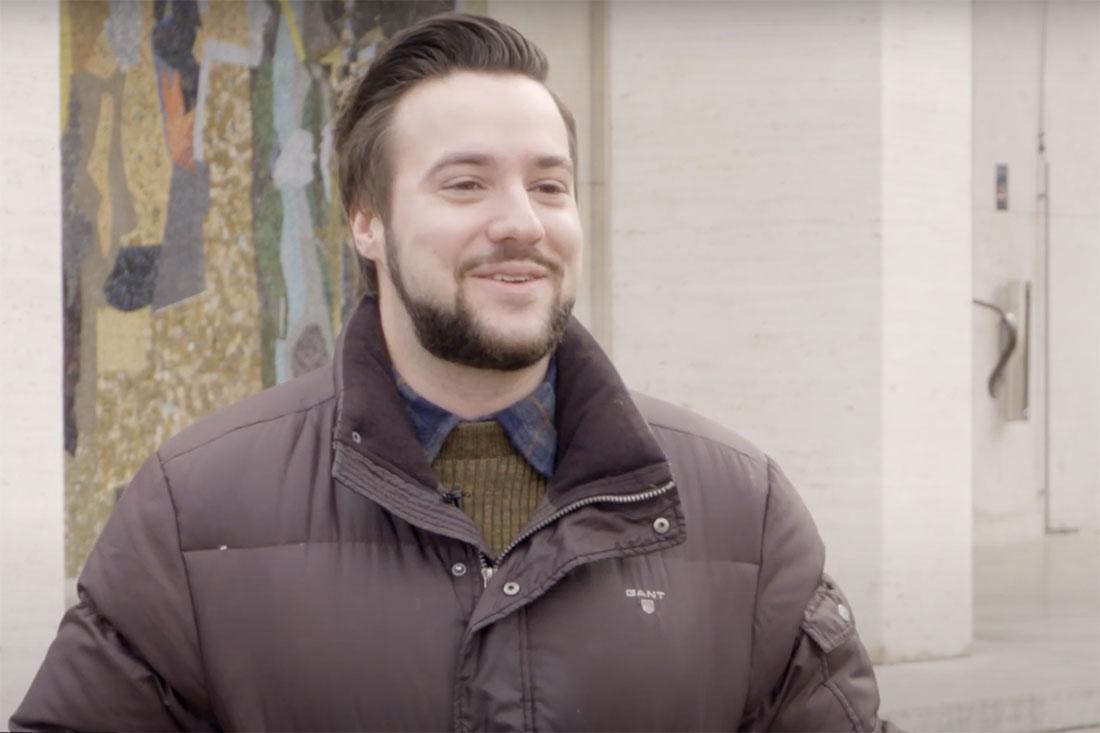 Junger Mann in Winterjacke steht vor der Universität Basel von seinen Zusatzlinsen.
