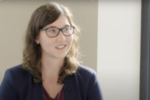 Junge Frau mit Brille sitzt im Wartezimmer der Augenpraxis und erzählt von ihrer SmartSurface Behandlung.