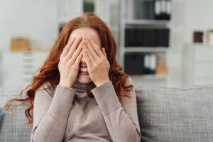 Junge rothaarige Frau hält sich beide Hände vor die Augen.