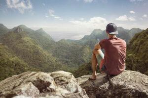 Junger Mann von hinten zu sehen. Er sitzt auf einem Felsen, trägt eine Mütze verkehrt rum, ein T-Shirt und eine Shorts. Sein Blick ist in die Ferne gerichtet. Unter und vor ihm liegen tropische Wälder. Am Horizont sieht man verschwommen eine Küste.
