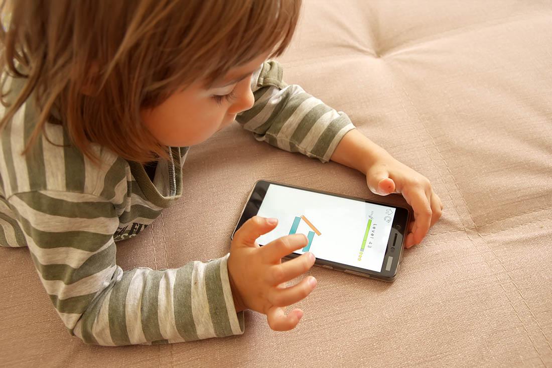 Kleinkind liegt auf dem Bett und spielt am Smartphone.