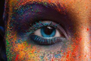 Augenbereich einer Frau mit blauem Auge, umgeben von buntem Farbpuder.