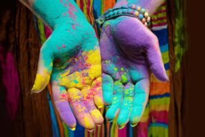 Zwei Hände voll mit oranger, gelber, violetter und blauer pudriger Farbe.