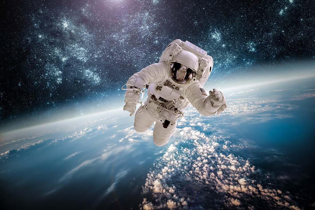Astronaut fliegt im Weltall, unter ihm die Erde.