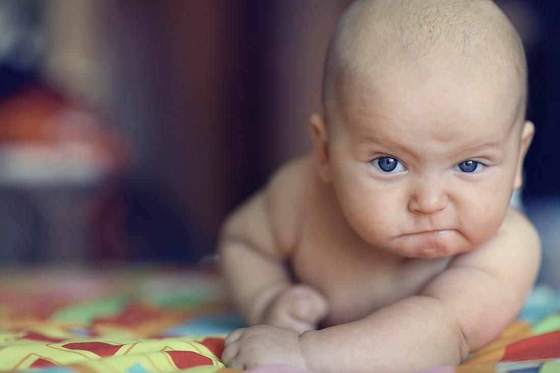 Baby mit dunkelblauen Augen schaut grimmig in die Kamera.