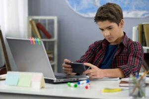 Junge im Alter von 11 Jahren sitzt am Pult. Er schaut auf sein Smartphone dass er in seinen beiden Händen halt. Auf dem Pult hat er zudem einen geöffneten Laptop.