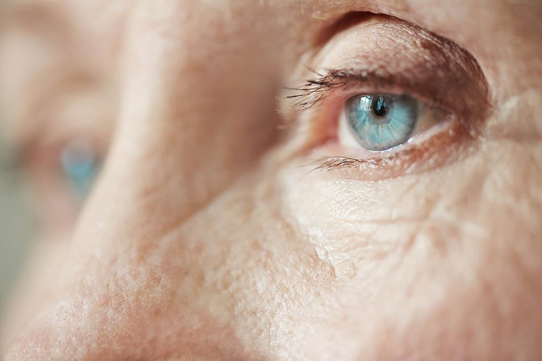 Nahaufnahme von blauen Augen einer älteren Dame. Sie schaut traurig an der Kamera vorbei.