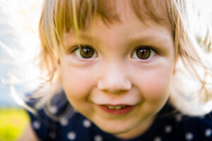 Junges Mädchen schaut mit grossen, braunen Augen direkt in die Kamera. Es lächelt und halt blonde Haare.