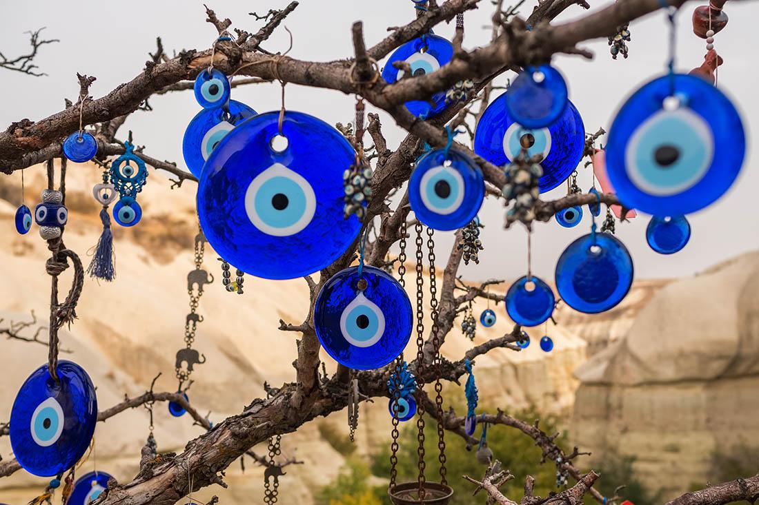 Mehrere Nazar-Amulette aus Glas hängen an einem Baum ohne Blätter. Im Hintergrund ist eine Felslandschaft zu sehen. Die Amulette sind rund. Der äusserste Ring ist blau, dann folgt ein dünner weisser Ring, ein hellblauer und in der Mitte ist ein schwarzer Punkt.